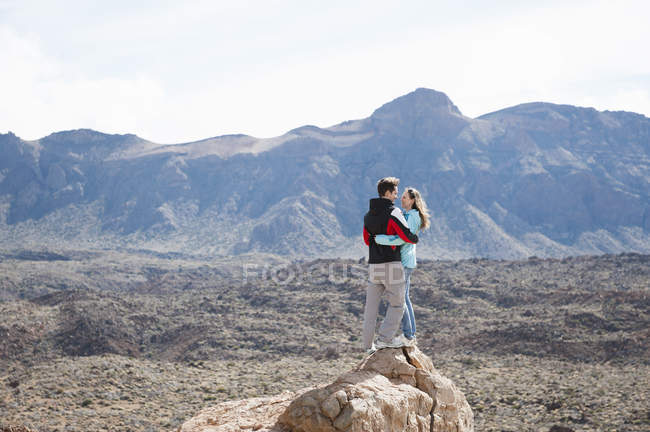 Mid adult couple standing on rock, Teide National Park — Stock Photo