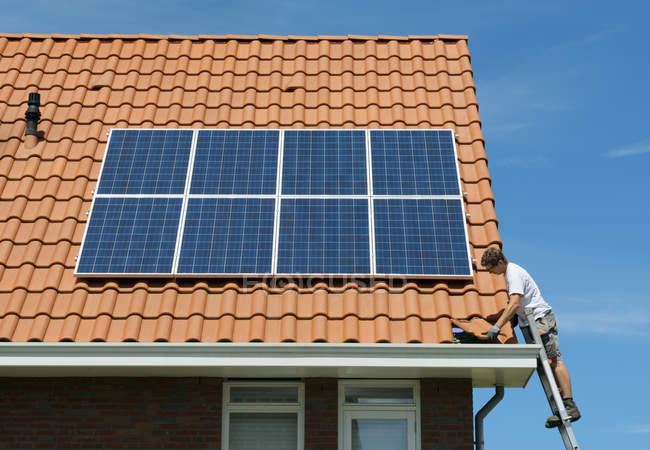 Worker checking installation of solar panels on roof of new home, Netherlands — Stock Photo