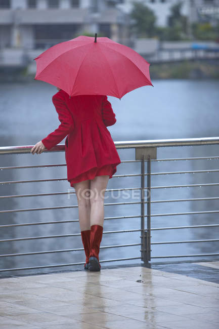 Young woman in red waiting by waterfront — Stock Photo
