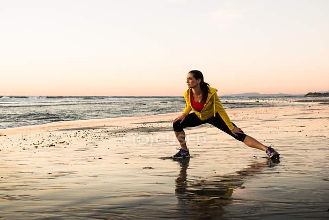 Runner feminino alongamento na praia — Fotografia de Stock