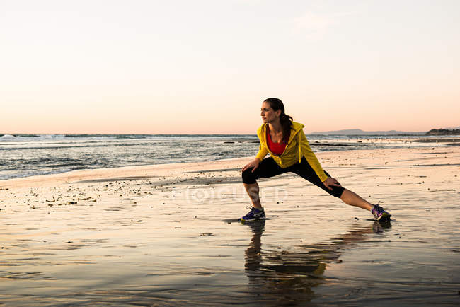 Female Runner stretching on beach — Stock Photo