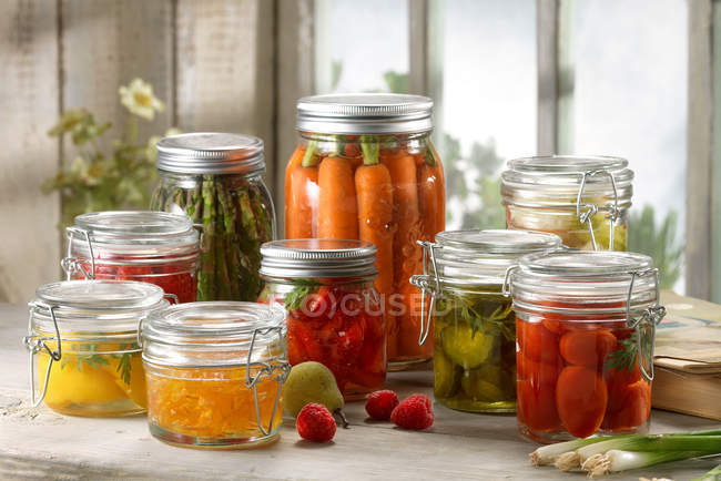 Variety of fruit and vegetables pickled in jars — Stock Photo