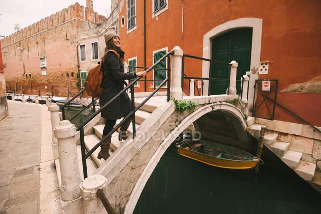 Woman crossing bridge over canal, Veneza, Itália — Fotografia de Stock