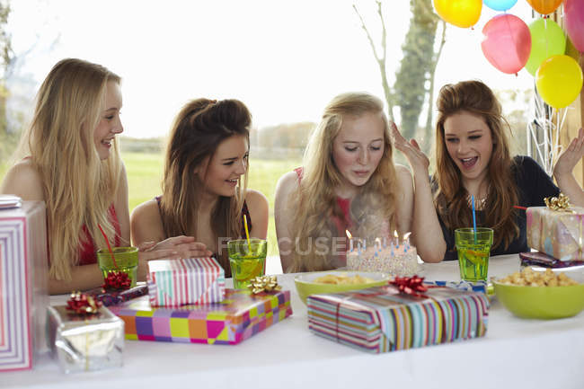 Teenage girl blowing out birthday candles with friends — Stock Photo