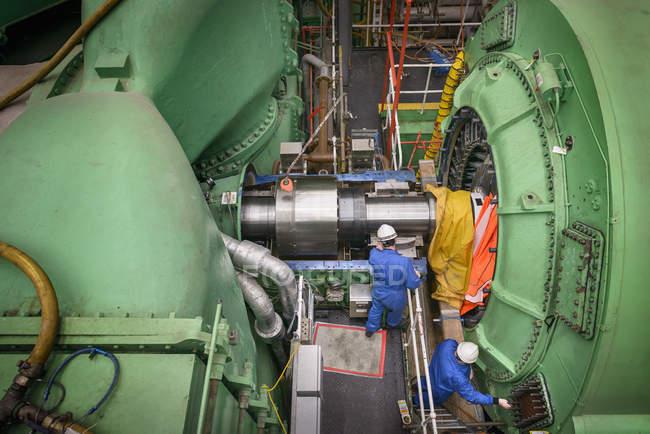 Ingegneri che lavorano sulla riparazione dell'alloggiamento della turbina durante l'interruzione della centrale elettrica, vista ad alto angolo — Foto stock