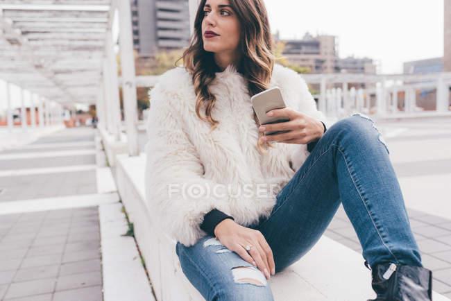 Jovem mulher sentada ao ar livre, segurando smartphone, olhando para longe — Fotografia de Stock