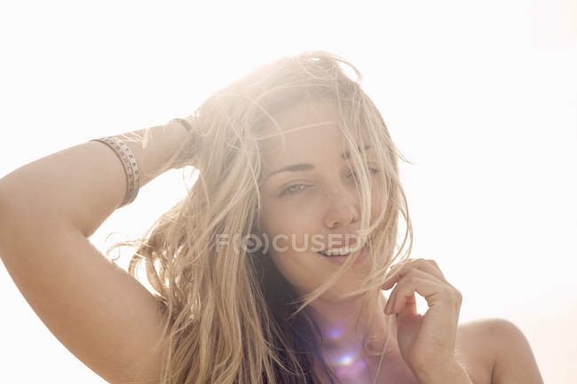 Portrait of young woman with hand in blond hair against sunlit sky — Stock Photo