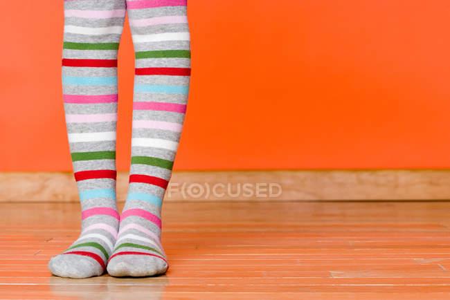 Ragazza bambino piedi indossare collant a strisce — Foto stock