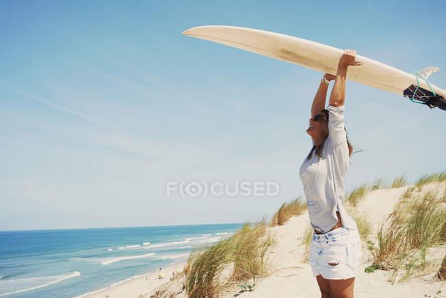 Femme avec planche de surf sur la plage, Lacanau, France — Photo de stock