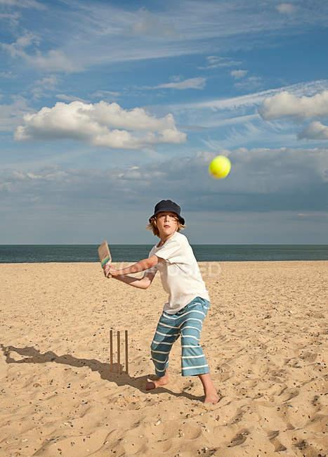Хлопчик грає крикет на пляжі — стокове фото