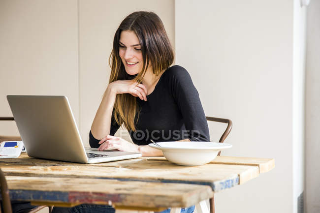 Young woman sitting at table in apartment with breakfast, reading on laptop — Stock Photo