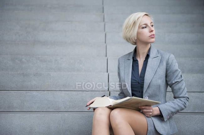 Geschäftsfrau Lesebuch auf Treppe — Stockfoto
