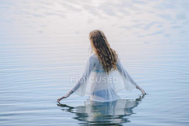 Вид сзади на молодую женщину, стоящую на волнистой поверхности озера — стоковое фото