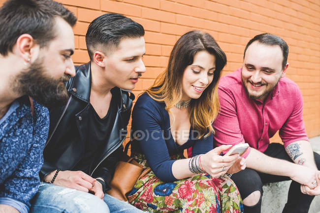Group of friends looking at message on cellphone together — стокове фото