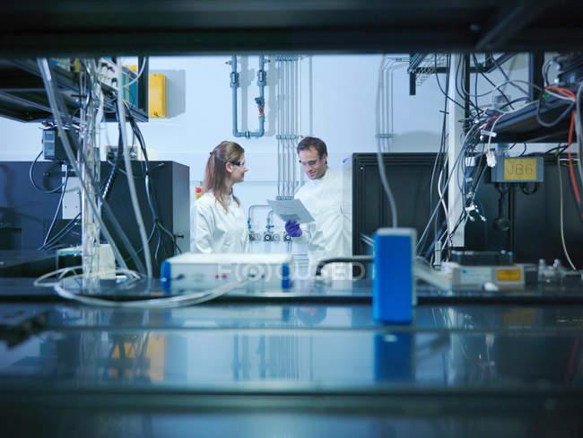 Wissenschaftler sprechen und betrachten Notizen im Labor mit Laser-Experiment — Stockfoto