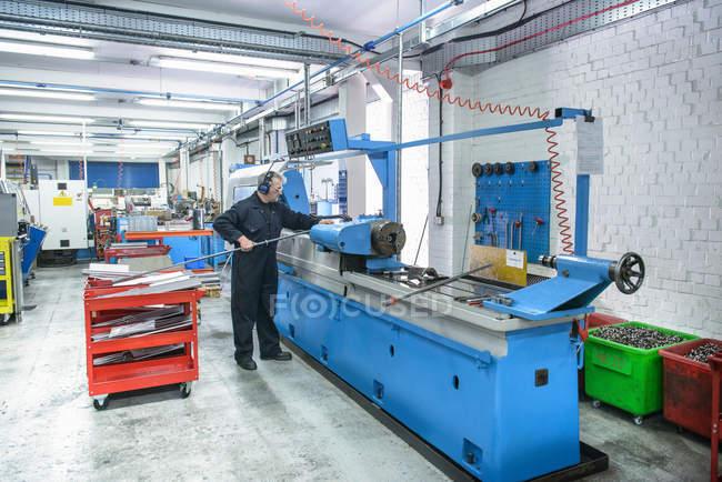 Инженер готовит промышленный токарный станок на машиностроительном заводе — стоковое фото