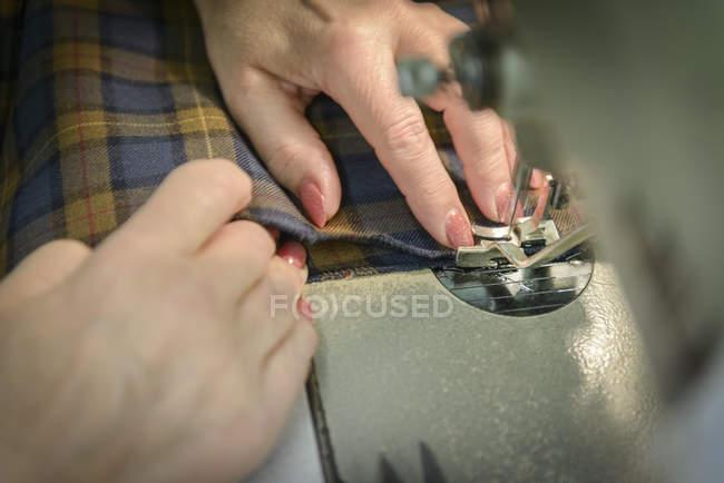 Close-up tiro de vestuário de costura trabalhador numa fábrica de roupas — Fotografia de Stock