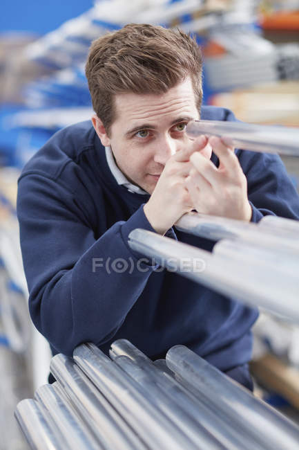 Ouvrier d'usine inspectant des tiges métalliques dans une usine de stores à rouleaux — Photo de stock