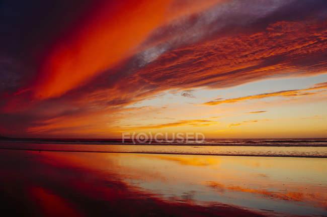 Vista da praia molhada refletindo o pôr do sol céu laranja — Fotografia de Stock