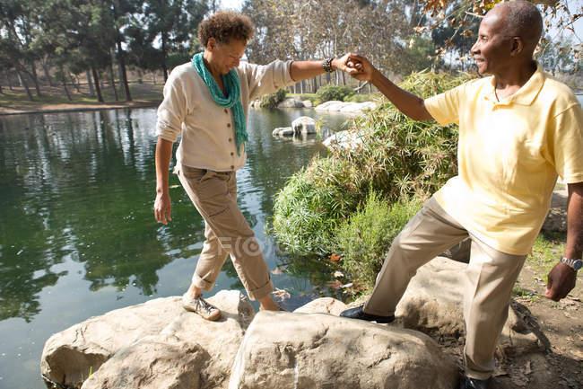 Porträt eines älteren Ehepaares, das in einem Park am See auf Felsen tritt — Stockfoto