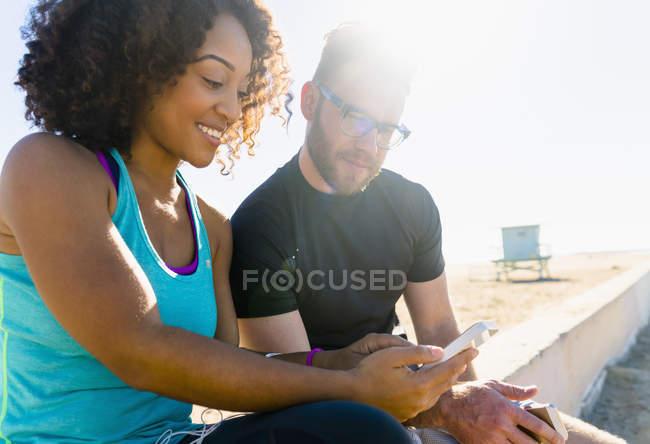 Пара сидящих на стене, смотрящих на смартфон — стоковое фото