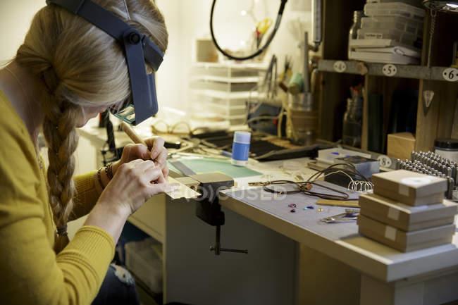 Fabricant féminin de bijoux utilisant l'outil dans le studio de conception — Photo de stock