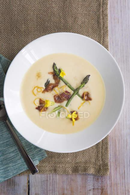 Draufsicht der Suppe mit Spargel und Zitrone Zitronenschale garnieren — Stockfoto