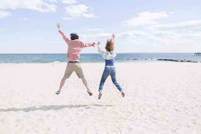 Vue arrière du couple sautant en plein air sur la plage — Photo de stock