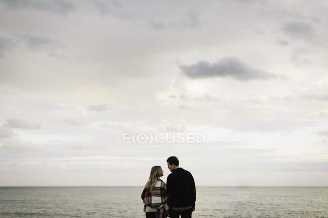Pareja joven al aire libre, junto al mar, vista trasera - foto de stock