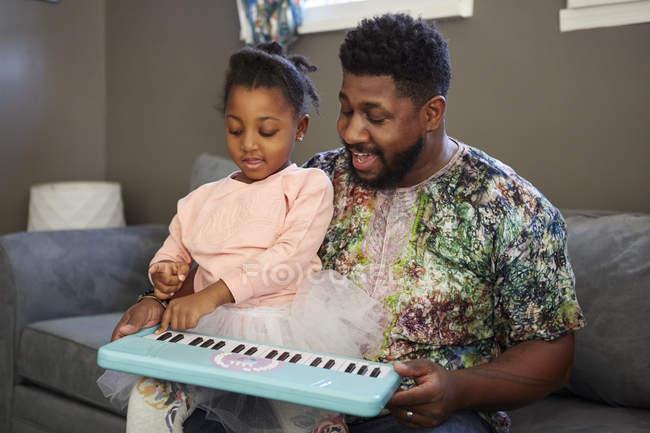 Девушка на диване с отцом, играющим на клавиатуре — стоковое фото
