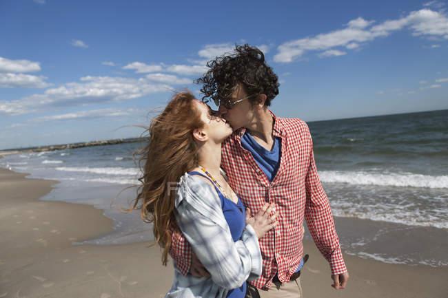 Romántica pareja besándose en la playa - foto de stock
