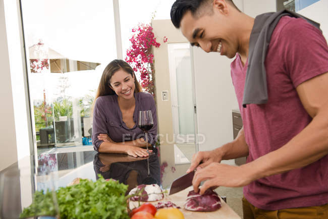 Couple chatting and chopping vegetables in kitchen — Stock Photo