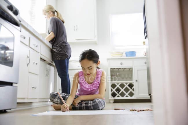 Девушка сидит на полу кухни и рисует — стоковое фото