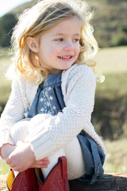 Cute blond girl sitting on log hugging knees — Stock Photo
