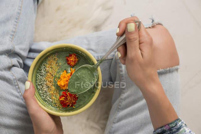 Vista aérea de la mujer sosteniendo cuenco de comida adornada con flores - foto de stock