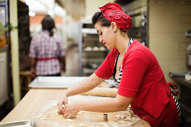 Young baker preparing food in kitchen — Stock Photo