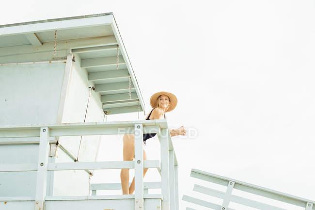 Mujer con traje de baño en la torre de salvavidas y mirando hacia otro lado - foto de stock
