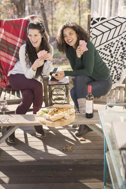 Дві молоді жінки друзі сміятися, граючи карткова гра на патіо — стокове фото