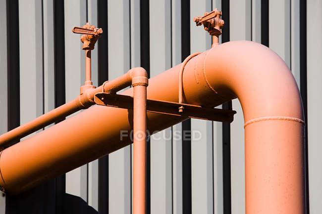 Vista ravvicinata dei tubi industriali arancione luminosi esterno pianta — Foto stock