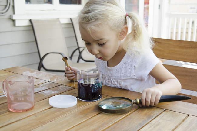Chica joven haciendo experimento de ciencia - foto de stock