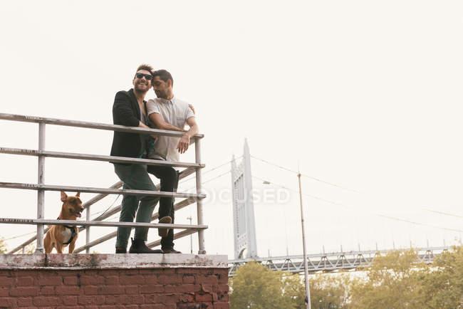Ласкавий молодий чоловік пара на Ріверсайд з собакою, Асторія, Нью-Йорк, США — стокове фото