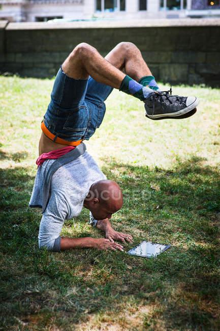Jeune homme faisant handstand en utilisant la tablette — Photo de stock