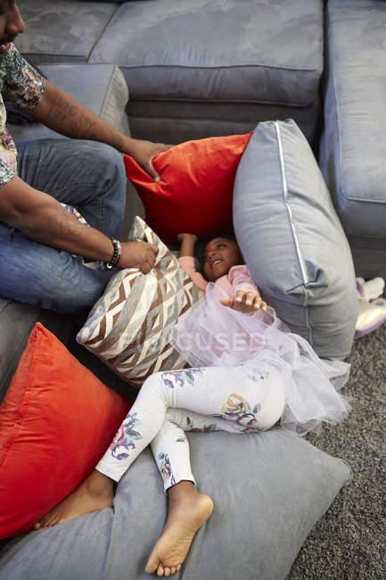 Девушка среди подушек играет с отцом — стоковое фото