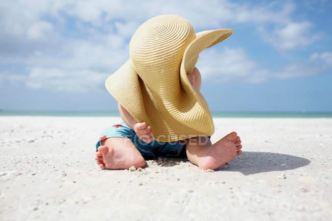 Bambino che gioca con il cappello da sole della madre sulla spiaggia — Foto stock