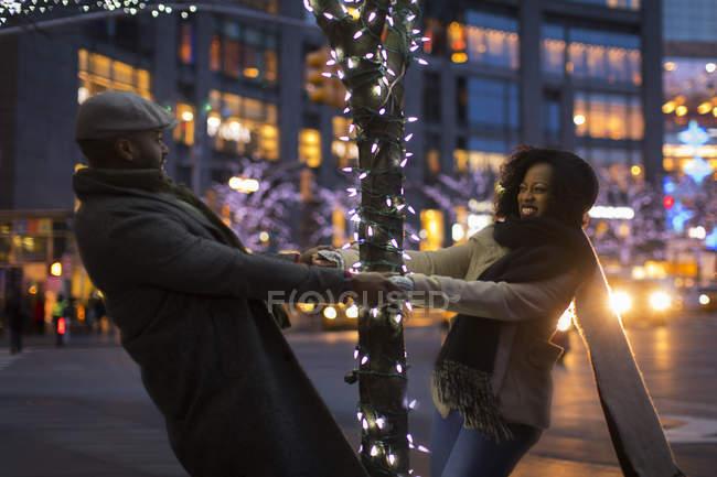 Romantiche coppie felici che godono città durante le vacanze invernali che gira intorno all'albero con luci di vacanze — Foto stock
