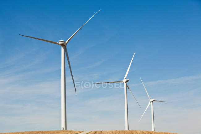 Three wind turbines side by side with blue cloudy sky — Stock Photo