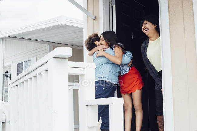 Grandmother and granddaughter hugging on porch — Stock Photo
