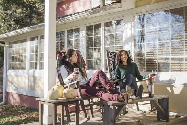 Двоє молодих подруг, які розслабляє на сонячних патіо з червоним вином — стокове фото