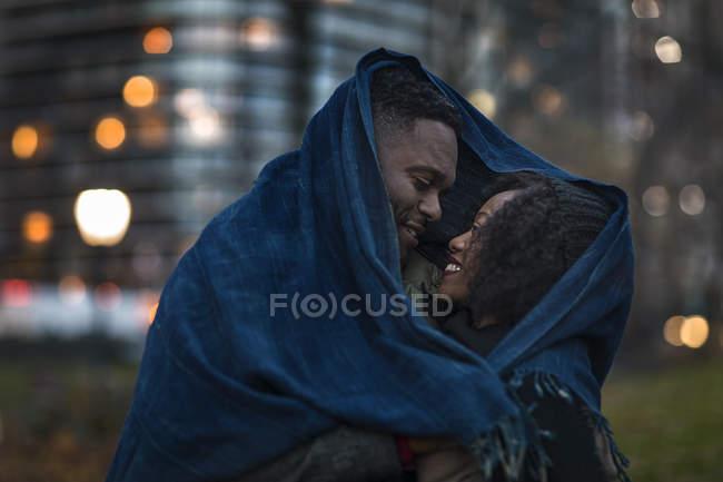 Romantiche coppie felici che godono città durante le vacanze invernali insieme avvolto sotto sciarpa — Foto stock