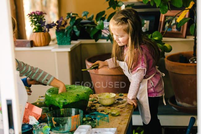 Mädchen beim naturwissenschaftlichen Experiment, mit der Hand in grüner schäumender Flüssigkeit — Stockfoto
